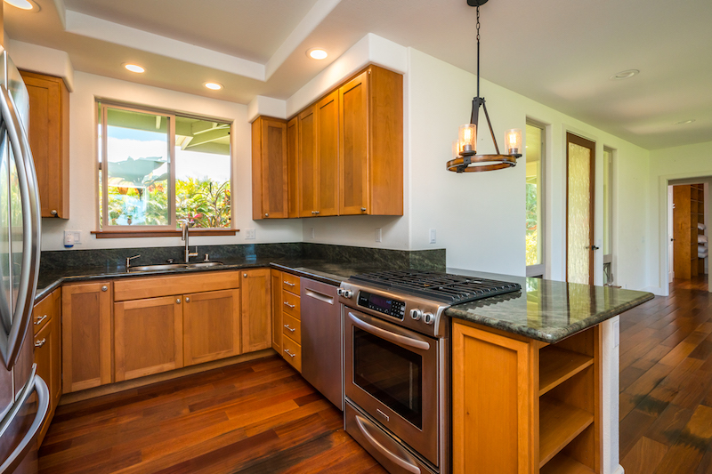 a well appointed kitchen with granite counters, quality counters and stainless steel appliances